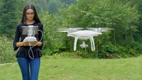 Young woman controlling drone with a transmitter remote control. Young woman controlling drone in field. Drone operator holding a transmitter remote control and stock video