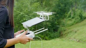 Young woman controlling drone with a transmitter remote control. Young woman controlling drone in field. Drone operator holding a transmitter remote control and stock video footage