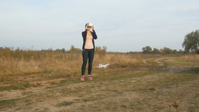 Young woman controlling drone with VR headset on field at sunset stock video