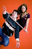 Young Woman Controls Man. Pretty young woman with baton holds young man around the throat to subdue him. Both young adults are dressed in trendy casual clothes stock images