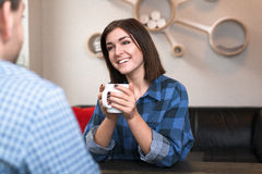 Young woman in conversation at a table holding a c. Young smiling woman in casual wear in a relaxed coversation with a man at a dining table, holding a warm Stock Photography