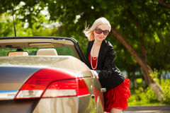 Happy blond fashion woman at the convertible car Royalty Free Stock Images
