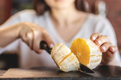 The girl cut the orange with a knife royalty free stock photo