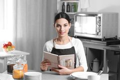 Young woman with cookbook sitting. At kitchen table Royalty Free Stock Photos