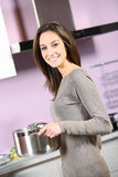 Young woman cooking. Portrait of smiling young woman cooking Royalty Free Stock Photography