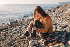 Young woman cooking coffee on sea beach royalty free stock image