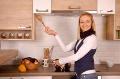 Cooking dinner. Young woman cooking dinner in a rustic kitchen Royalty Free Stock Photography