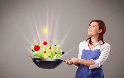 Young woman cooking fresh vegetables Stock Photo