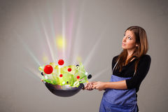Young woman cooking fresh vegetables Royalty Free Stock Photos
