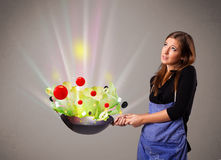 Young woman cooking fresh vegetables Stock Images