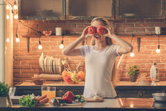 Young woman cooking healthy fresh meal at home. Young female cooking healthy fresh meal in the kitchen fun Royalty Free Stock Image