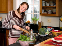 Young woman cooking healthy greens. Royalty Free Stock Photos
