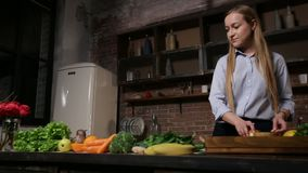 Young woman cooking healthy smoothie in kitchen. Attractive woman bringing wooden tray with ingredients for vegetarian smoothie and laying out fruits on the