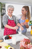 Young woman cooking with her mother in the kitchen. Stock Images