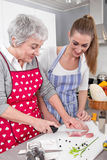 Young woman cooking with her mother in the kitchen. Stock Photos