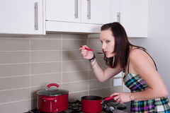 Young woman cooking in kitchen Stock Images