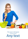 Young woman cooking in the kitchen on blue Royalty Free Stock Photo