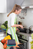 Young woman cooking in the kitchen Royalty Free Stock Images