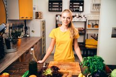 Young woman cooking on the kitchen, healthy food. Vegetarian diet, fresh vegetables and ts Stock Images