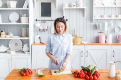 Young woman cooking in the kitchen at home. A woman cuts a cucumber and vegetables with a knife. Bright, stylish kitchen Stock Image