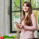 Young Woman Cooking in the kitchen at home. Girl in the kitchen holds a tablet and looks at the camera Stock Images