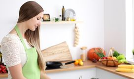 Young woman cooking in the kitchen. Housewife slicing fresh salad stock photos