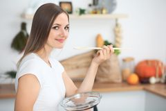 Young  woman cooking in a kitchen. Housewife tasting soup by wooden spoon.  Stock Photo