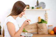 Young woman is cooking in a kitchen. Housewife is tasting the soup by wooden spoon. Royalty Free Stock Image