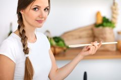 Young woman is cooking in a kitchen. Housewife is tasting the soup by wooden spoon royalty free stock photos
