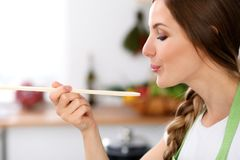 Young woman is cooking in a kitchen. Housewife is tasting the soup by wooden spoon.  Stock Images