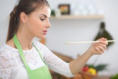 Young  woman cooking in a kitchen. Housewife tasting soup by wooden spoon.  Royalty Free Stock Photography