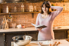 Young woman is cooking in the kitchen with joy. She is standing and holding a book of recipe. Stock Image