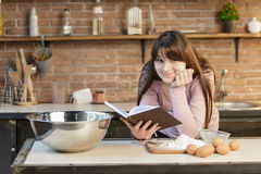 Young woman is cooking in the kitchen with joy. She is standing and holding a book of recipe. She is smiling. Young woman is cooking in the kitchen with joy. She Royalty Free Stock Photography