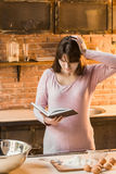 Young woman is cooking in the kitchen with joy. She is standing and holding a book of recipe. In the kitchen on the table lie eggs, flour and a book. A woman Royalty Free Stock Photos