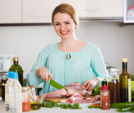 Young woman cooking lamb for dinner at home Royalty Free Stock Photography