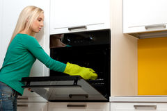 Young woman cooking with oven. Beautiful young woman cooking with oven Stock Photos