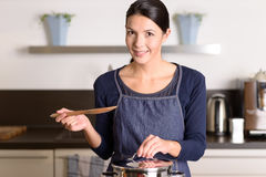 Young woman cooking over the stove. Young woman cooking the food for dinner over the stove in her kitchen standing holding the lid of a stainless steel saucepan Stock Photography