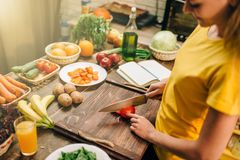 Young woman cooking on recipes, healthy bio food. Preparing. Vegetarian diet, fresh vegetables and fruits Stock Photography