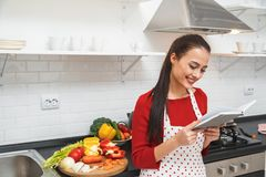 Young woman cooking romantic dinner at home reading receipt stock photography