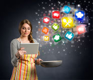 Young woman cooking using the tablet Stock Photos