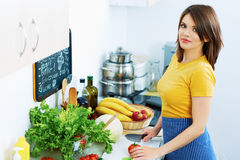 Young woman cooking vegetable in kitchen. Royalty Free Stock Photo