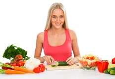 Young woman cooking. Vegetable salad royalty free stock images