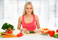 Young woman cooking. Vegetable salad Stock Image