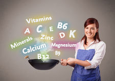 Young woman cooking vitamins and minerals Royalty Free Stock Images