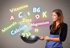 Young woman cooking vitamins and minerals Royalty Free Stock Photography