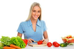 Young woman cooking. Vegetable salad stock images