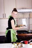 Young woman cooks dinner. In the kitchen Stock Image