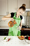 Young woman cooks dinner Royalty Free Stock Photography