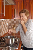 Young woman cooks the dinner Stock Images