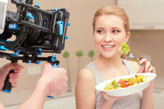 Young woman cooks salad. Good cooking. Smiling lady holding plate with salad and tasting some lettuce from it standing before camera Stock Images